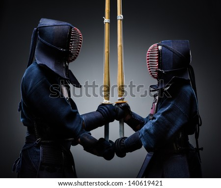 Two kendo fighters with shinai opposite each other. Japanese martial art of sword fighting - stock photo