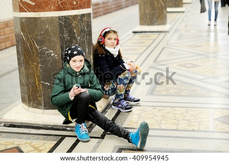 Two kid girls in fashion outfits waitng for train in the subway