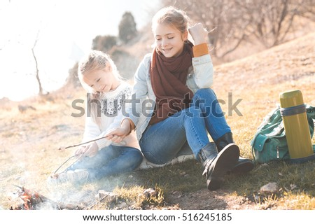 Two kid girls toasting marshmallow in fire outdoors. Childhood.