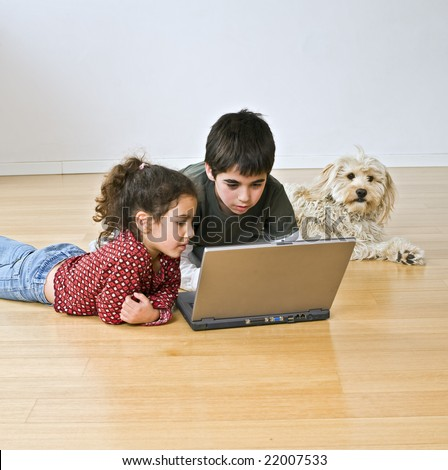 two kids and a dog with laptop computer on the floor