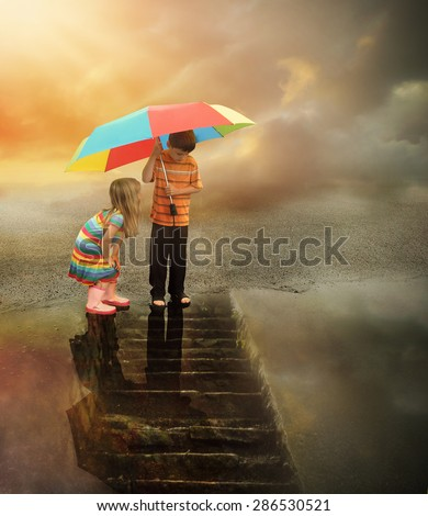 Two kids are looking down at a rain puddle of water with stairs in the reflection. The boy is holding a rainbow umbrella for a weather or imagination concept. - stock photo