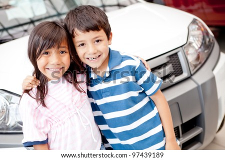 Two kids at the dealer buying a family car - stock photo