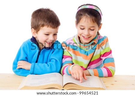 Two kids at the table reading the book, isolated on white - stock photo