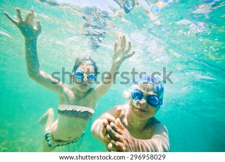 Two kids - boy and a girl, about seven years old are swimming underwater in a sea or ocean. - stock photo