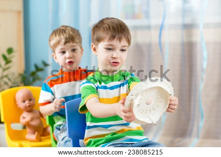Two kids boys playing role game and riding on carriages made from chairs - stock photo