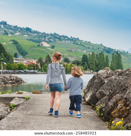 Two kids, brother and sister walking by the lake, wearing frocks and blue shoes, back view - stock photo