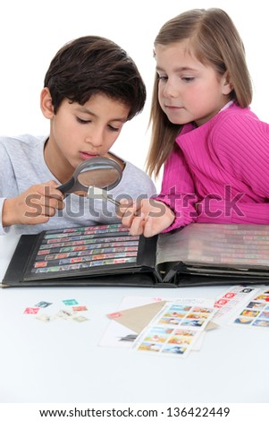 Two kids collecting stamps. - stock photo