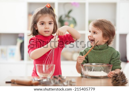 Two kids cooking at home and have a lot of fun - stock photo
