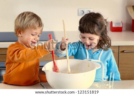 Two kids cooking in a domestic kitchen - stock photo