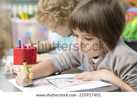 Two kids drawing at kindergarten - stock photo