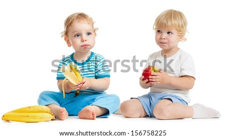 Two kids eating healthy food isolated on white - stock photo
