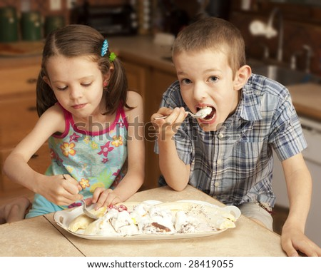 two kids eating large plate of ice cream - stock photo