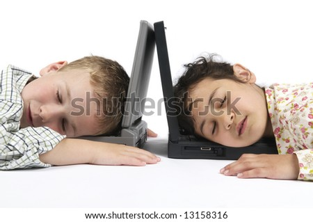 Two kids fallen asleep on their laptops while doing their homework for school. - stock photo
