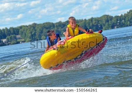 two kids flying through the air on a tube - stock photo