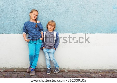 Two kids, girl and little boy, posing outdoors, standing against blue wall, toned image - stock photo