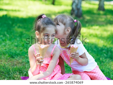 Two kids girls sisters whispering eating ice cream on background of grass - stock photo