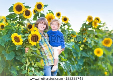 Two kids, handsome boy and his cute baby sister, playing in a sunflower field on a sunny summer day - stock photo