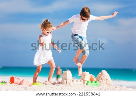 Two kids having fun on summer vacation crushing sandcastle - stock photo