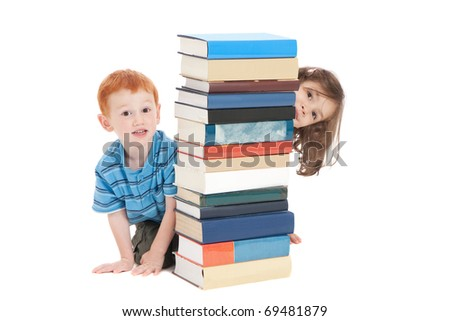 Two kids hiding behind stack of books. Isolated on white.