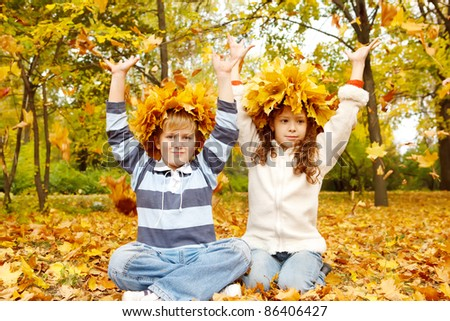Two kids in head wreaths catching yellow leaves