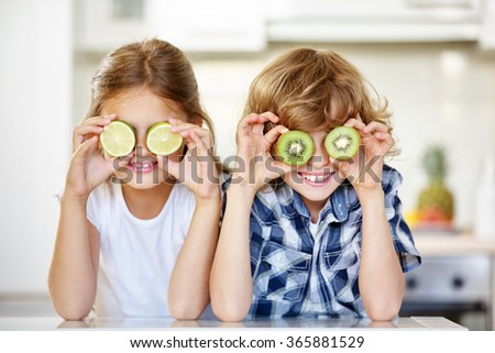 Two kids in kitchen hiding their eyes behind fruits - stock photo