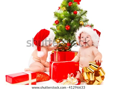 Two kids in Santa hats beside Christmas tree - stock photo