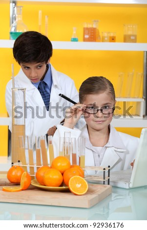 Two kids in science laboratory - stock photo