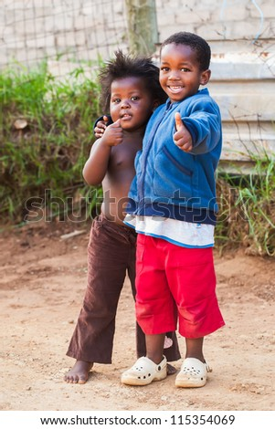 Two kids in the street showing a thumbs up to the photographer. - stock photo
