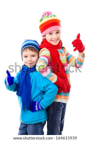 Two kids in winter clothes and thumbs up sign, isolated on white - stock photo