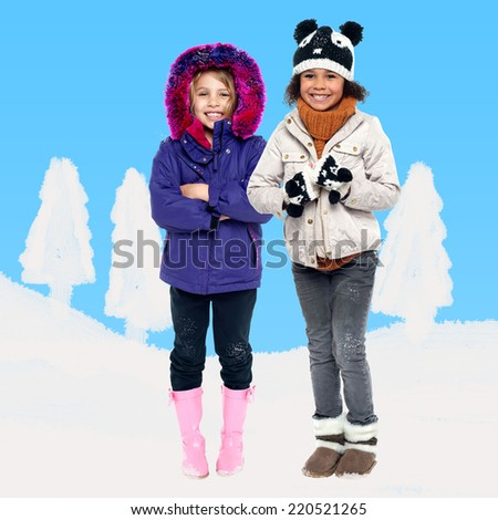 Two kids in winter wear against snow background - stock photo