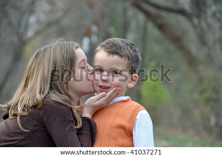 two kids kiss while on a walk in autumn - stock photo
