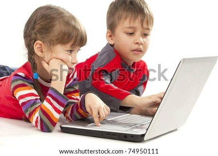 Two kids looking at notebook - laying flat on the floor