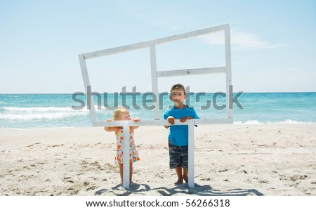 two kids looking out through wooden window on sea background - stock photo