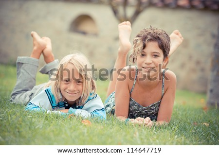 Two kids lying on top of grass,Italy