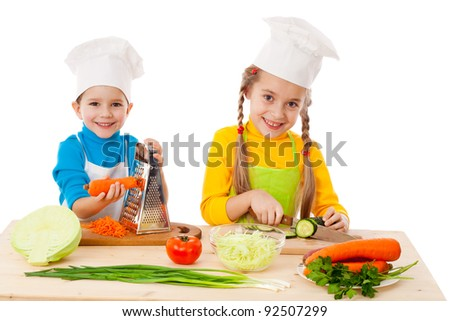 Two kids making salad, cooking the vegetables. Isolated on white - stock photo