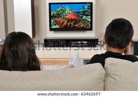 Two kids on couch watching TV, having a great time - a series of WATCHING TV images. - stock photo