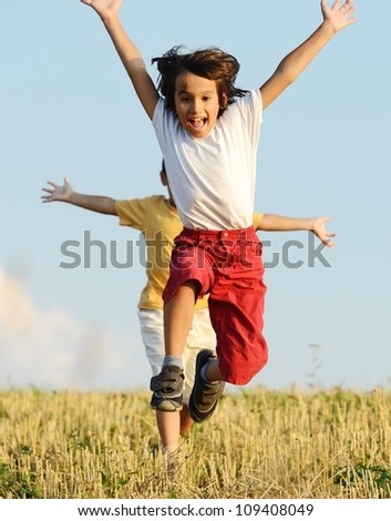 Two kids on field running - stock photo