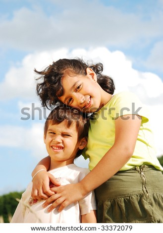 Two kids outdoor sitting on green ground and smiling - stock photo