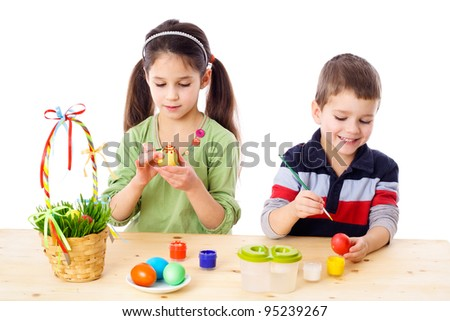 Two kids painting easter eggs, isolated on white - stock photo