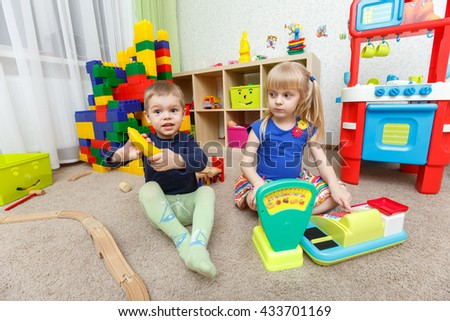 Two kids play role game in toy shop at home