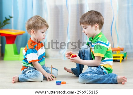 Two kids play with wooden toy sitting on the floor - stock photo