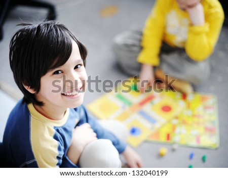 Two kids playing a game of cards - stock photo