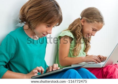 Two kids playing and surfing the web on digital tablet and laptop.