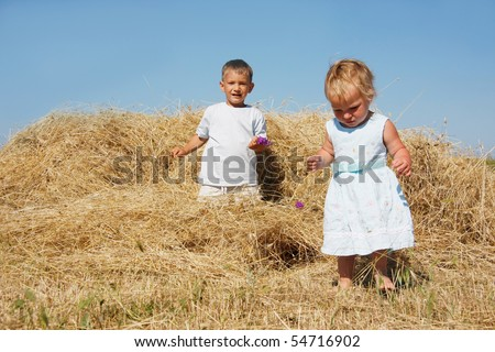 two kids playing in hay - stock photo