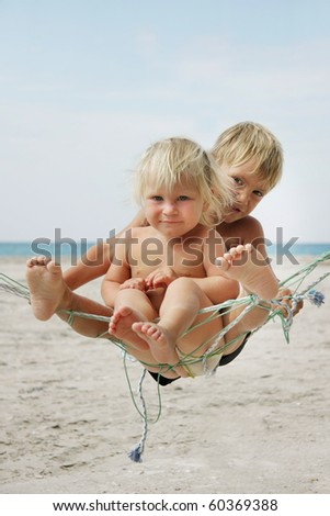 two kids playing in self-made hammock - stock photo