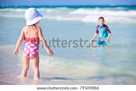 Two kids playing in water at Caribbean coast in Mexico - stock photo