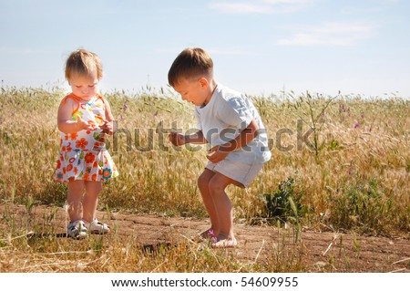 two kids playing on country road