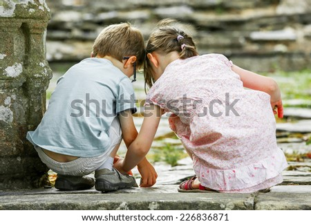 Two kids playing on the ground next to a mossy stone - stock photo