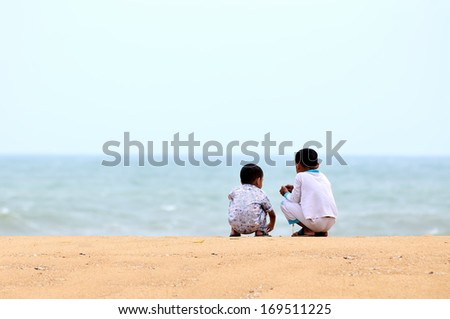 Two kids playing on the sand beach - stock photo