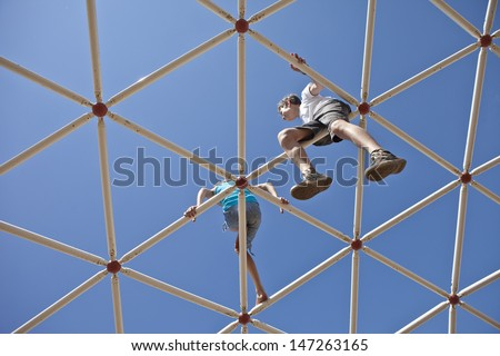two kids playing together on monkey bars, view up toward sky - stock photo